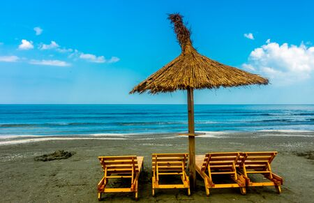 davenport: Seaside beach with lounge chairs and straw umbrella. Stock Photo