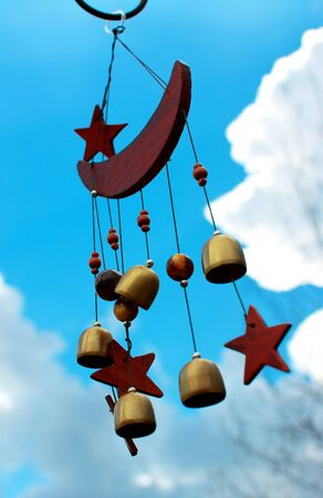 chimes: Moon and stars wind chimes with blue sky background.