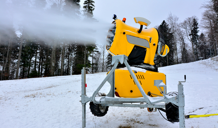 a slope: Yellow snow cannon on ski slope.