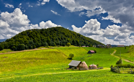 sheepfold: Mountain landscape with sheepfold on green lawn, forest hill in background and blue sky. Stock Photo
