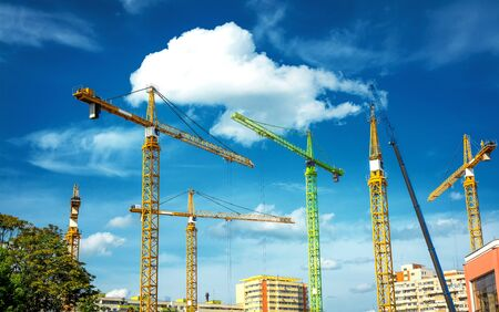 windlass: Construction site with many colored cranes. Stock Photo