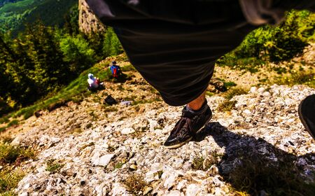 escalate: Leg of a climber on rock.
