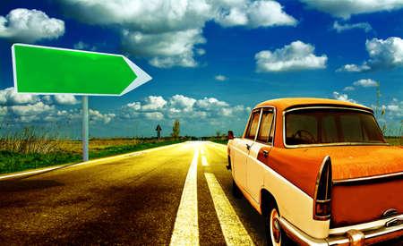 shiny car: Vintage car on shiny road with traffic arrow sign.