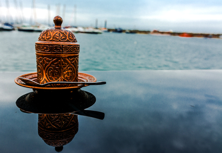 motifs: Bronze oriental cup of coffee with motifs.