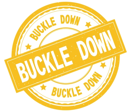 BUCKLE DOWN , written text on yellow round rubber vintage textured stamp. Stock Photo