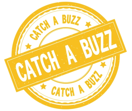 CATCH A BUZZ , written text on yellow round rubber vintage textured stamp. Imagens