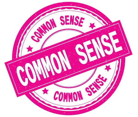 COMMON SENSE , written text on pink round rubber vintage textured stamp. Stock Photo
