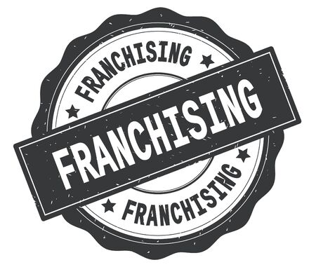 FRANCHISING text, written on grey, lacey border, round vintage textured badge stamp. Stock Photo