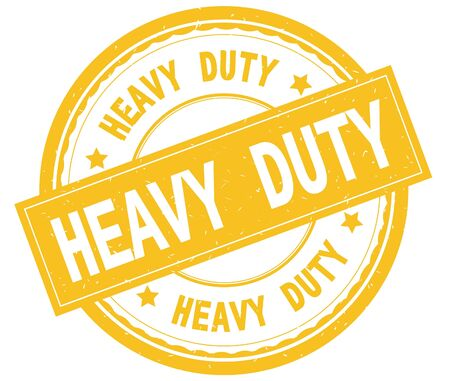 HEAVY DUTY , written text on yellow round rubber vintage textured stamp. Stock Photo
