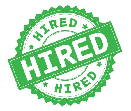 HIRED green text round stamp, with zig zag border and vintage texture. Stock Photo
