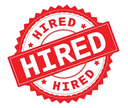 HIRED red text round stamp, with zig zag border and vintage texture. Stock Photo