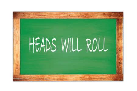 HEADS  WILL  ROLL text written on green wooden frame school blackboard.