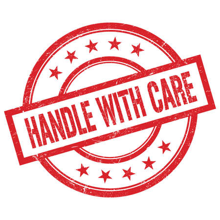 HANDLE WITH CARE text written on red round vintage rubber stamp. Stock Photo