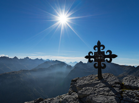christendom: Cross in front of mountain range with sun and blue sky