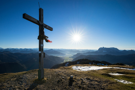 tirol: Summit cross with sun star an the Alps in background. Stock Photo