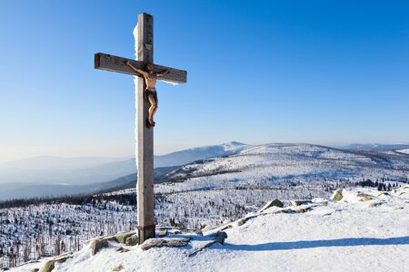 christendom: Winter landscape with summit cross and blue sky.