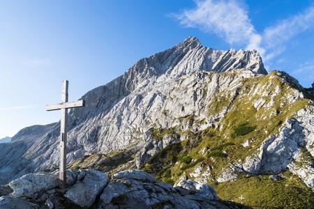pyramid peak: Summit cross of Mt. Osterfelderkopf with Mt. Alpspitze in background. Stock Photo