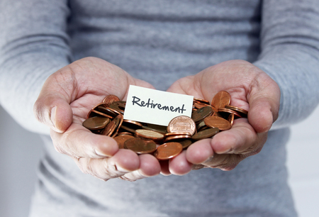 roth: Man holding coins for retirement Stock Photo