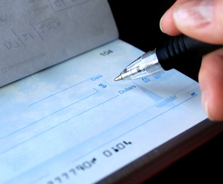 financial concept - writing a check. the account numbers on the check are not real.