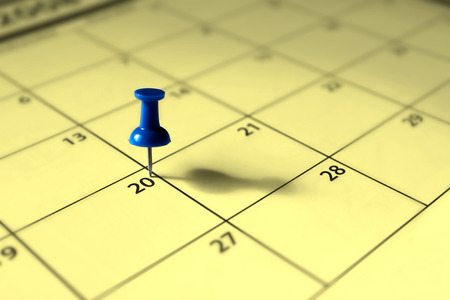 Office concepts - date marked on the calender with a colored push pin