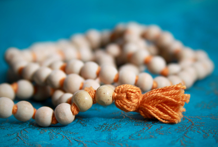 rosary with orange thread on blue background