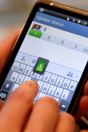 A mobile user updating status on a social networking mobile site for Facebook on an Android based mobile smartphone 新闻类图片
