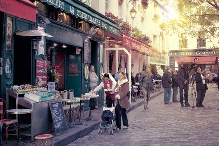 brasserie: street in montmartre paris with cafe and parisians, tourists enjoying the sunny day
