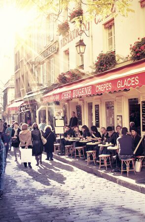 street in paris with cafe and parisians enjoying the sunny day Editöryel