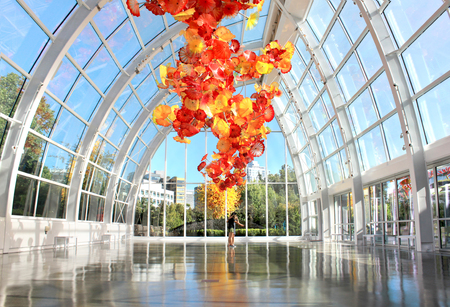 SEATTLE, July 29, 2017: Chihuly Garden and Glass museum featuring one of Dale Chihulys largest sculptures suspended from the ceiling of the glasshouse. City buildings are seen in the background.