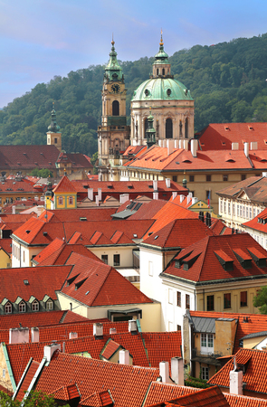 St Nicholas Church dome above red roof tops of Mala Strana and Petrin hill as backdrop in Prague, Czech Republic