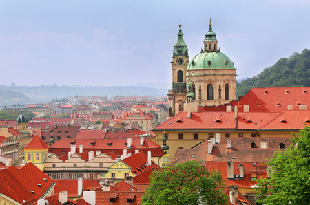 Beautiful cityscape and St Nicholas Church dome above red roof tops of Mala Strana, Prague, Czech Republic