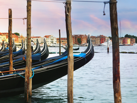 Beautiful sunset view of classic gondolas and skyline in background in Venice (Venezia), Italy
