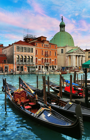 Venice, Italy, Jun 8, 2018: Moored Gondolas in foreground with San Simeon Piccolo church in the background in Venice, Italy 免版税图像