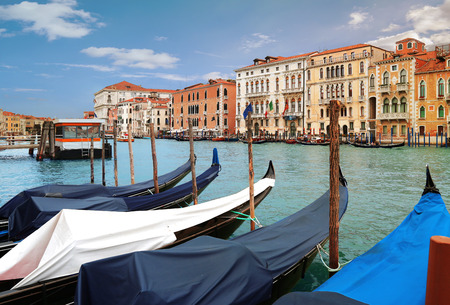 Venice, Italy, Jun 7, 2018: Moored Gondolas on Grand Canal with colorful buildings in the background in Venice, Italy 新闻类图片