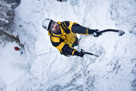 down beat: Man climbs up a frozen waterfall with ice ax.