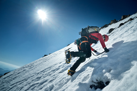 mountaineer climbs a North Face with crampons and ice ax