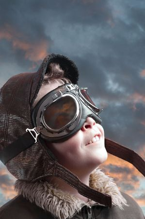 Boy dressed up in pilot´s outfit, jacket, hat and glasses.