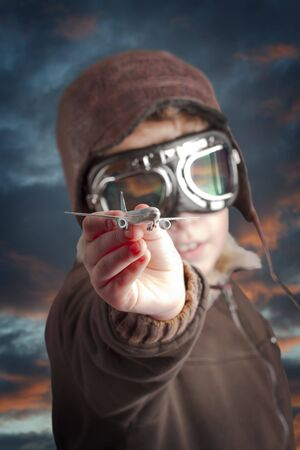 Boy dressed up in pilot�s outfit, jacket, hat and glasses. photo
