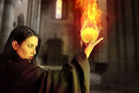 Young beautiful girl with fire sphere, sorcerer Stock Photo
