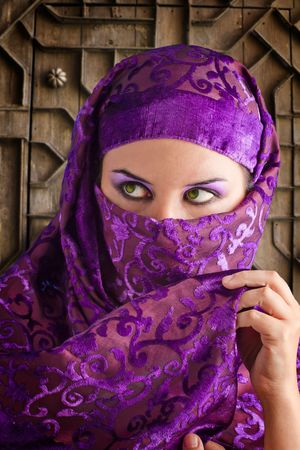 arabic woman: woman dressed in Arab costume, castle gate in the background Stock Photo
