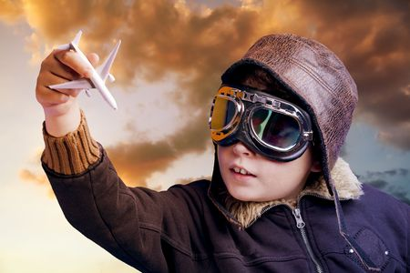Boy dressed up in pilot outfit at sunset sky photo