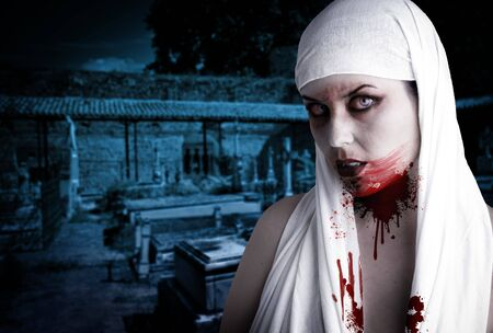 Female vampire with blood stains in a cemetery. Gothic Image halloween Stock Photo - 7816528