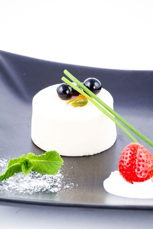 ambrosia: Vanilla mousse cylinder block crowned by cranberries with a bit of whip cream
