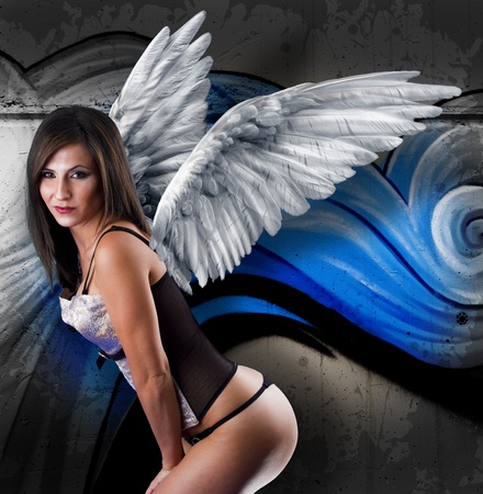 Beautiful young woman with white wings against graffiti wall. Stock Photo