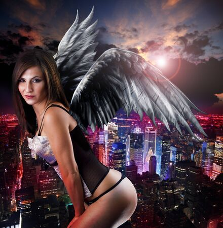 Woman with angel wings against city night skyline photo
