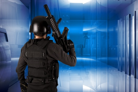 Armed man in protective cask with a machine gun on the modern building background.