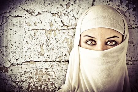 woman dressed in Arab costume, rusty wall in the background photo