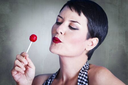 lolly pop: Portrait of lovely brunette with lolly pop, over rusty background Stock Photo