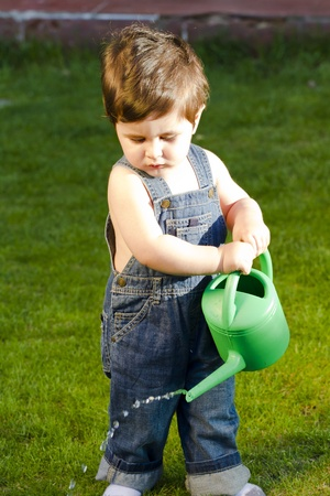 little baby gardener watering the grass and wearing work outfit Stock Photo