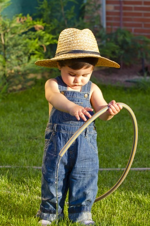 little baby boy gardener playing with sun shinning on his face Stock Photo